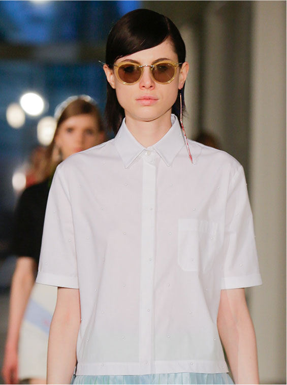 Model wearing a white blouse on the catwalk with Arthur Arbesser for Silhouette eyewear
