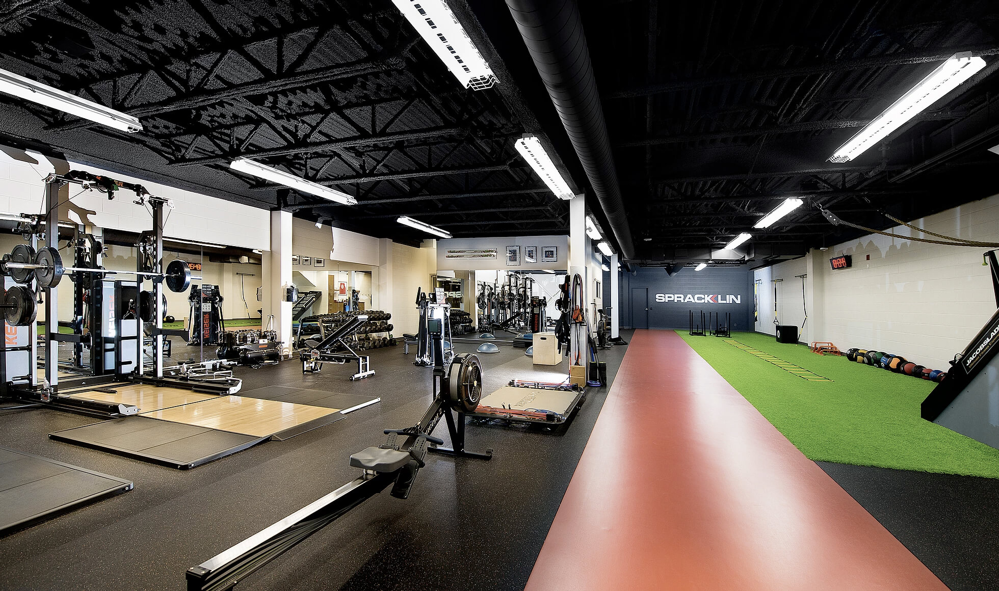 The gym at Hockey Etcetera, with various gym equipment on the left-hand side and a turf on the right-hand side.