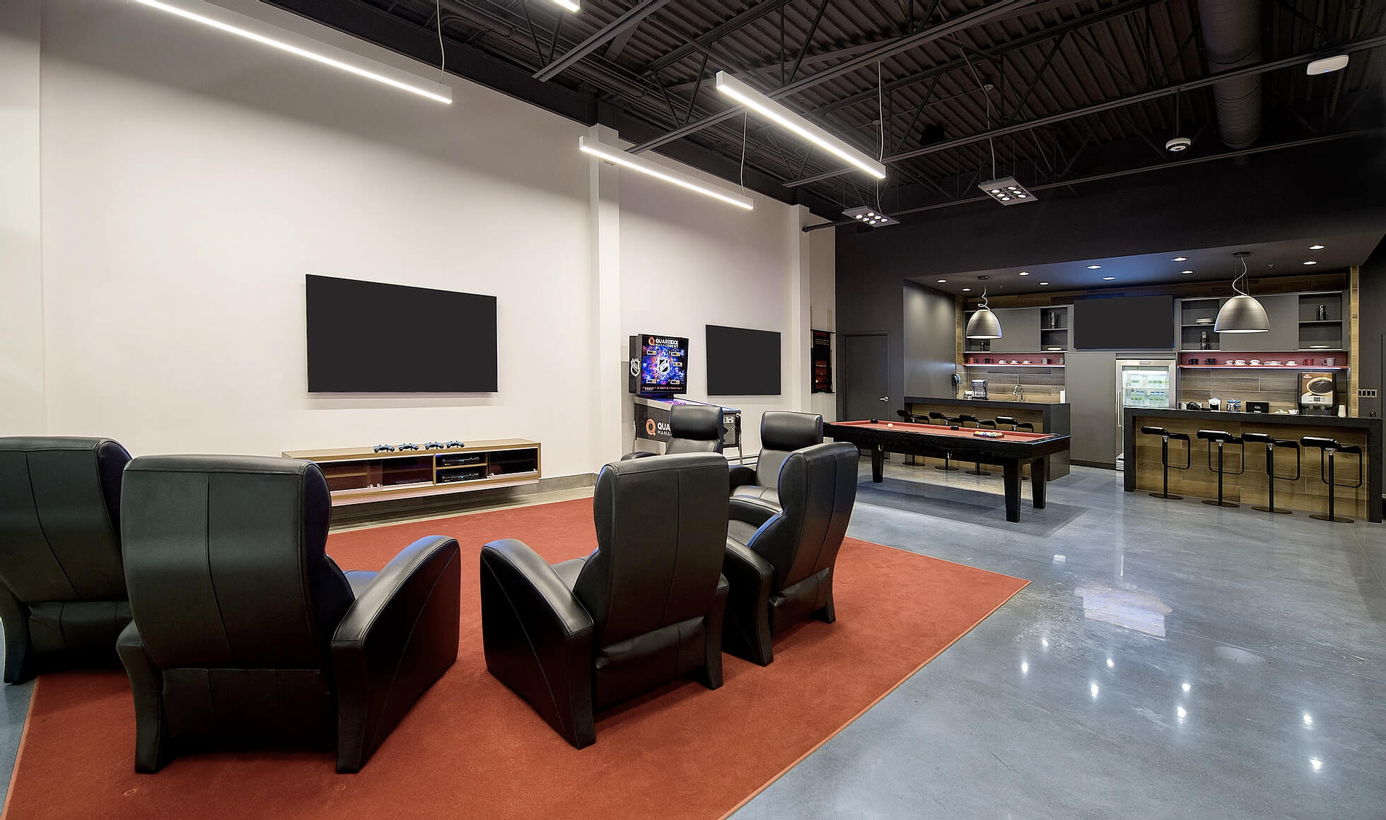 The player lounge at Hockey Etcetera with 4 comfy chairs overlooking a TV and gaming console. In the background is a nice kitchen and pool table.
