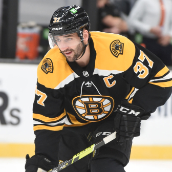NHL athlete Patrice Bergeron skating with the puck for the Boston Bruins