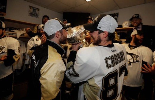 Sidney Crosby pouring a drink from the Stanley cup into Andy O'Briens mouth.