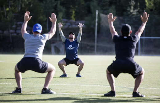 Andy O'Brien squatting with two clients in a soccer field with their arms raised to the sky.