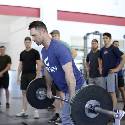 Andy O'Brien deadlifting while athletes watch him.