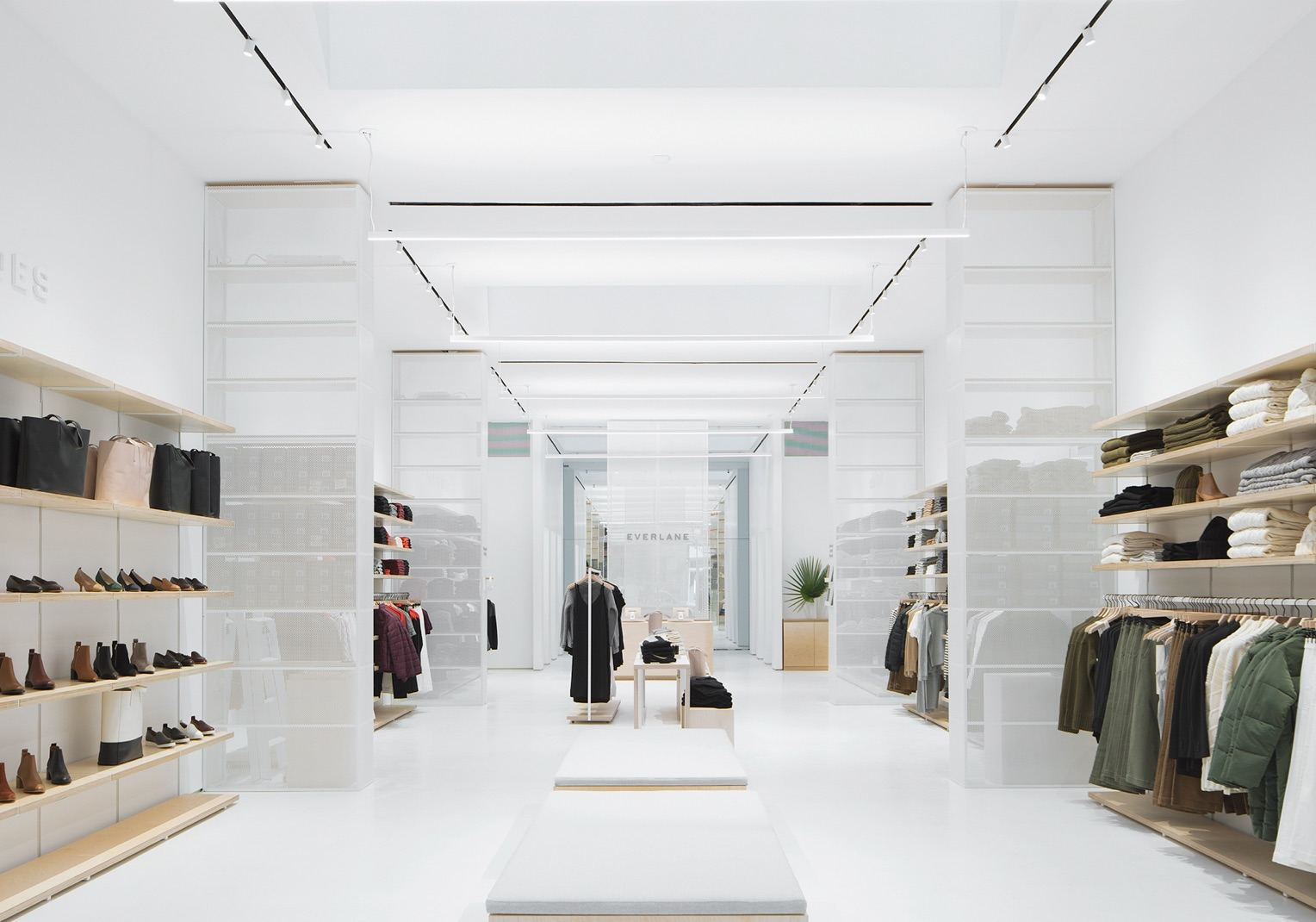 Inside view of Everlane's store. The room is mainly white with wooden System 1224 shelves along the walls displaying a variety of clothes.