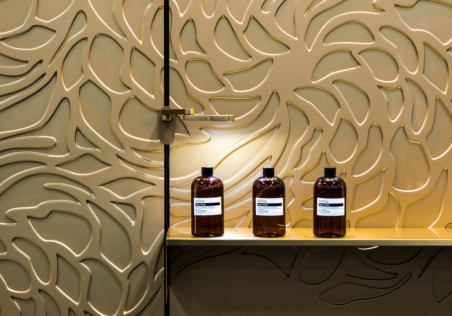 Close up shot of a golden floral patterned and metallic wall. A golden shelf along it is holding up three brown glass bottles.