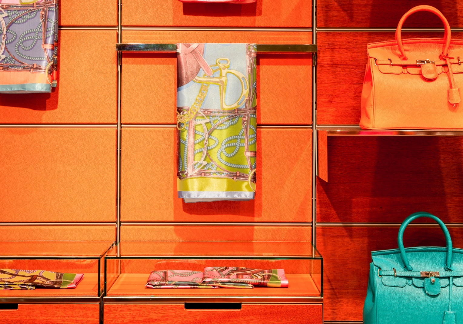 Bright orange panels decorate a wall holding golden shelves displaying various high end fabrics and purses.