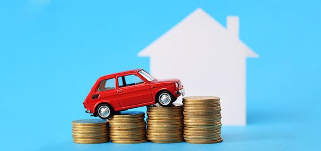 rode auto op munten met huis op de achtergrond