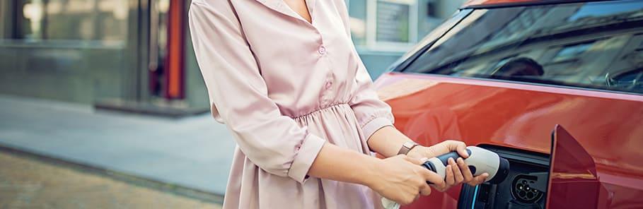 vrouw steekt laadstekker in auto