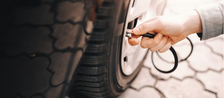 Man controleert bandenspanning auto