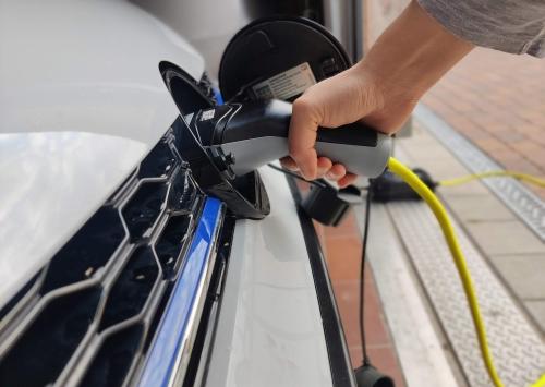 Hand mit Tankstutzen an Elektroauto