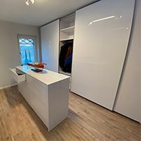 Ein weißes Garderobenzimmer mit großen Schränken und Schiebetüren