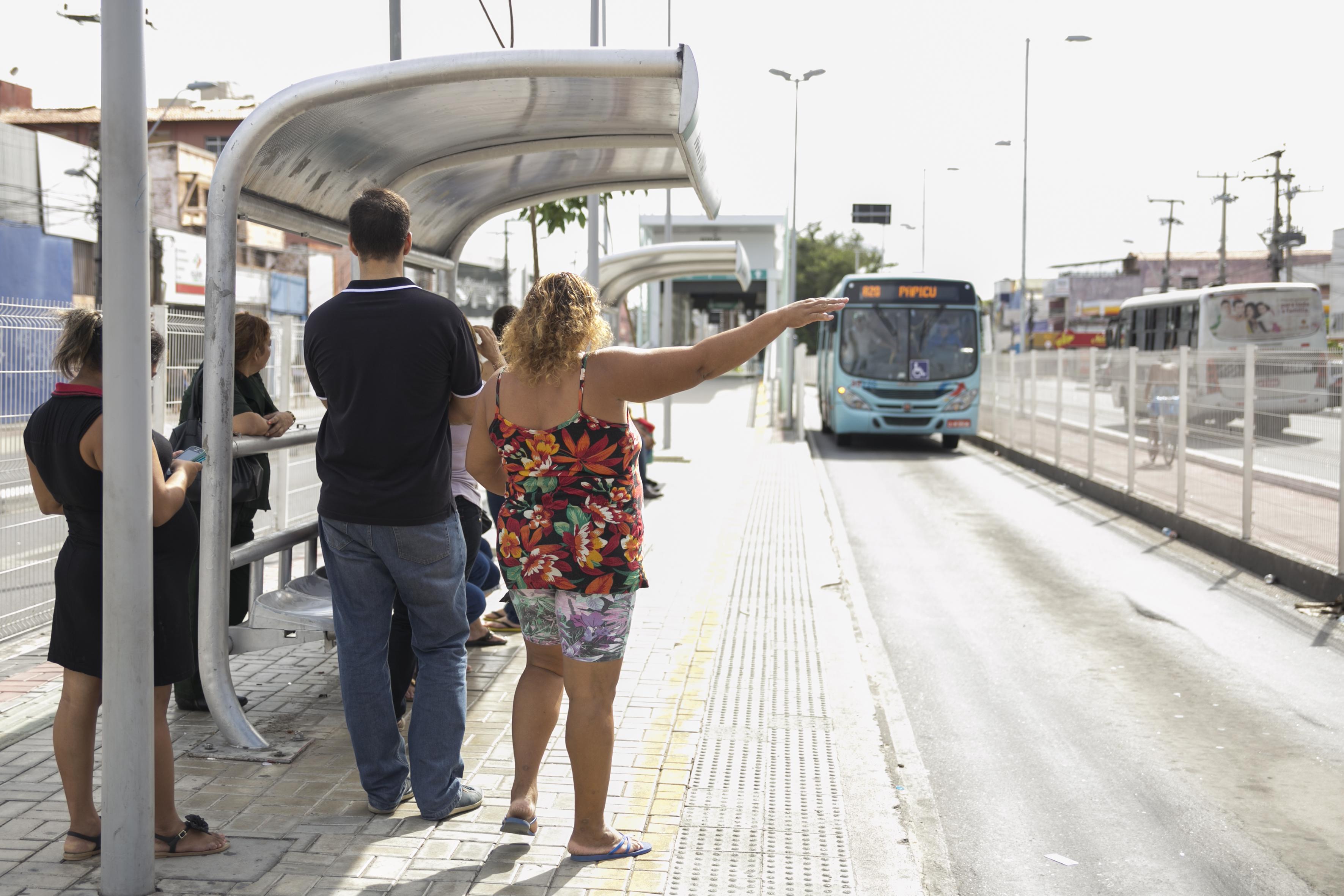 mulher no ponto de parada esperando o transporte público