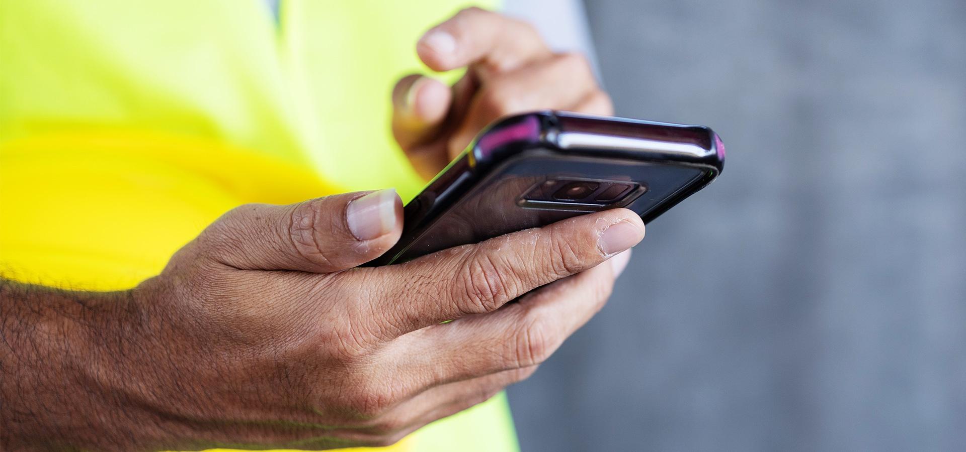 LINK Mobility - Mann mit Sicherheitsweste benutzt sein Smartphone, Kommunikation zu Ihren Kunden, Mitarbeiter und Lieferanten