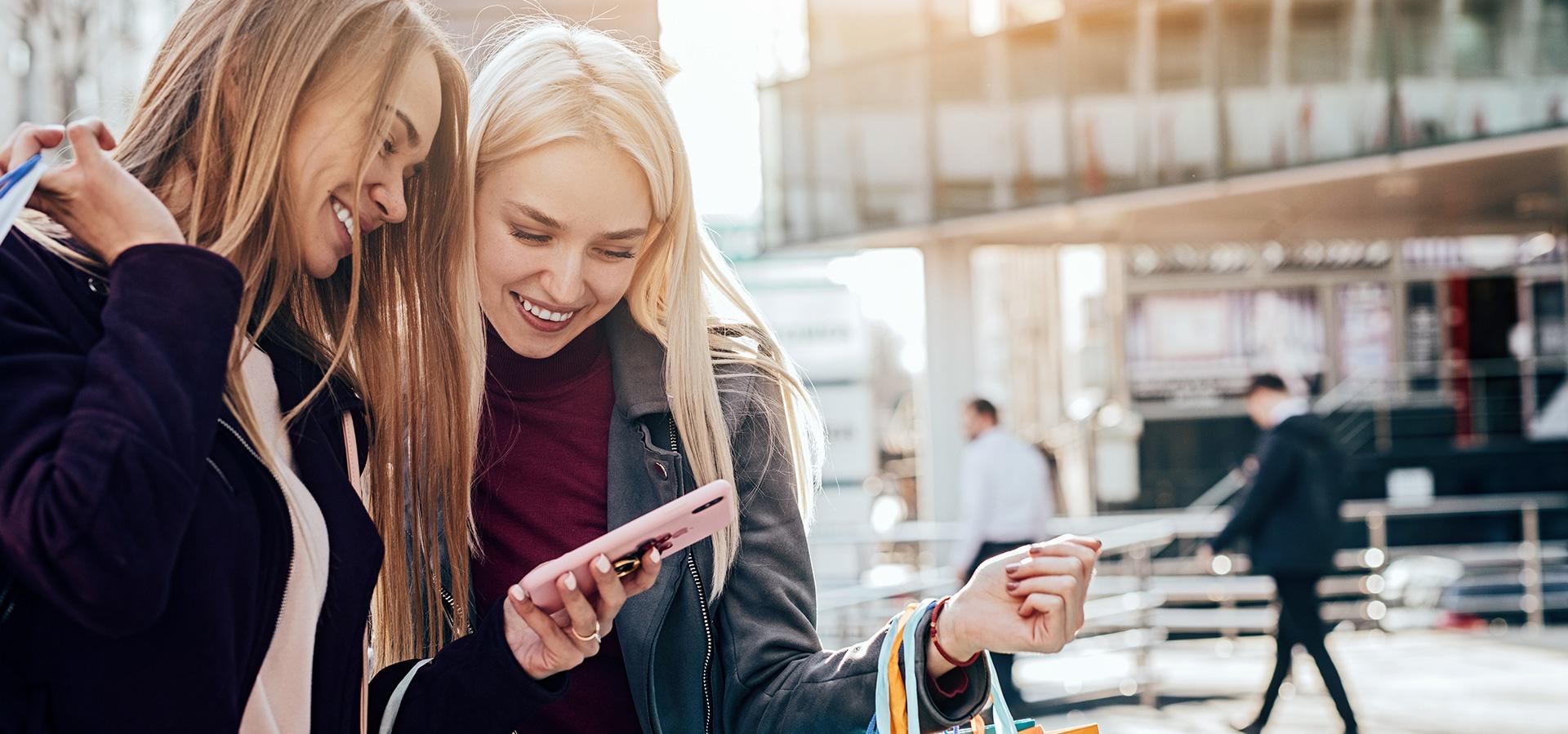 LINK Mobility - Zwei Frauen beim Shoppen mit ihrem Smartphone, Mehr Conversions für eCommerce & stationären Handel