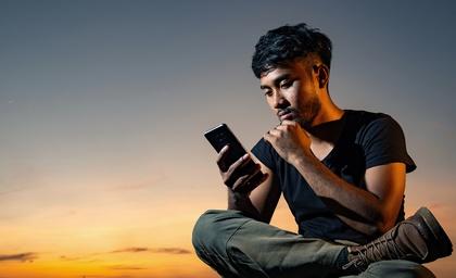 LINK Mobility - junger Mann benutzt sein Smartphone
