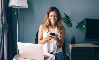 LINK Mobility - Glückliche junge Frau sitzt im Wohnzimmer vor ihrem Laptop und benutzt ihr Smartphone