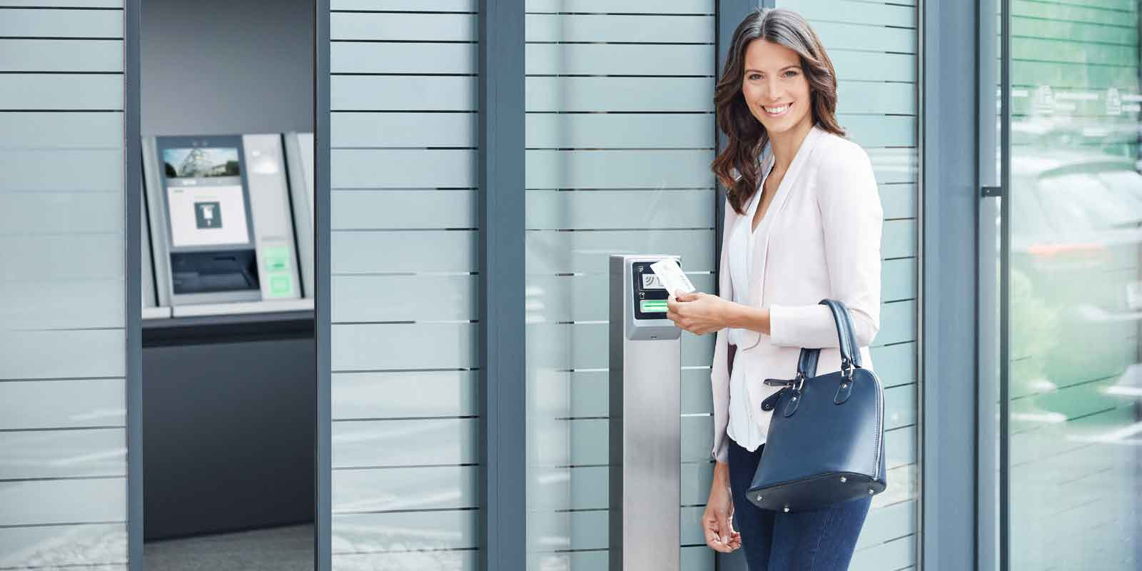 Woman opens the door to a bank branch by using KeBin S10 and authentication via NFC-technology
