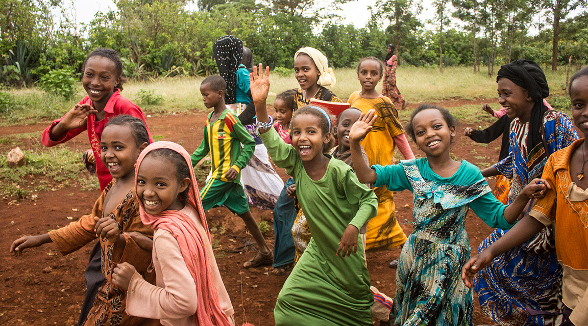 A group of girls laughing and waving