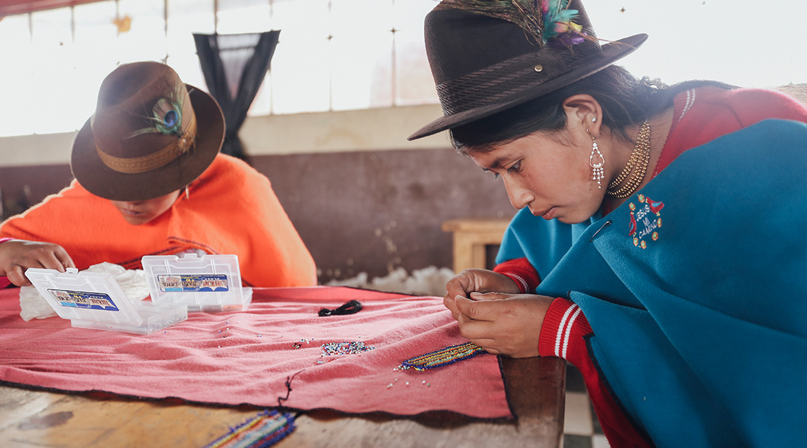 Young women in Ecuador beading jewelry