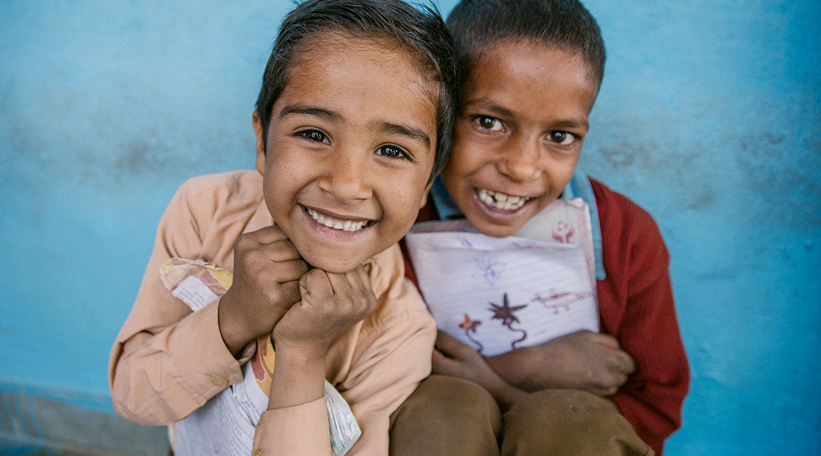 Two boys in India with textbooks smiling