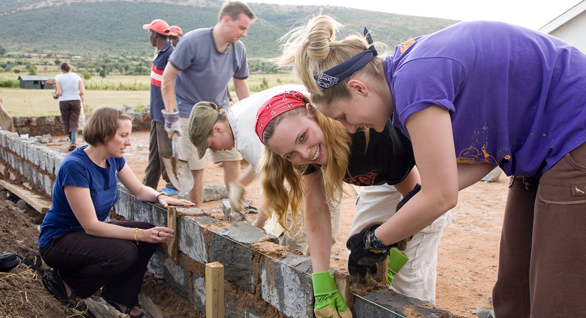 Young travellers building a wall of a development project