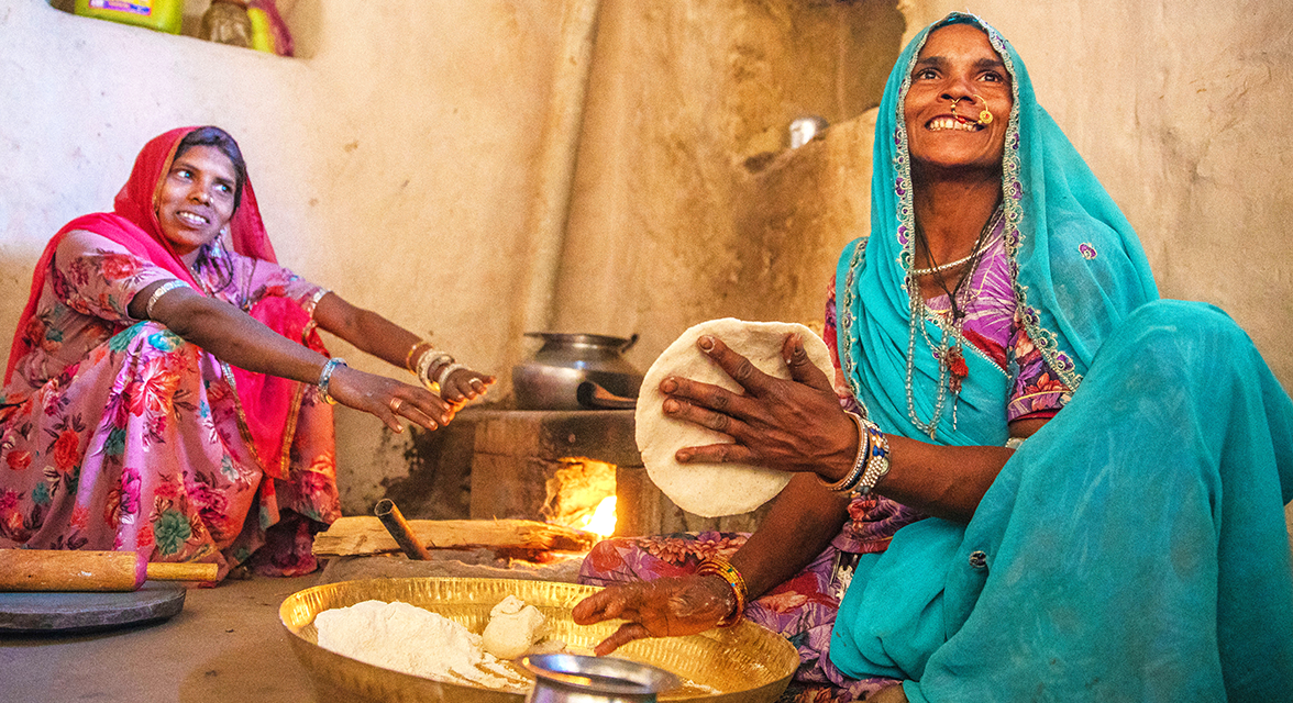 Local women cooking traditional chapatti in India