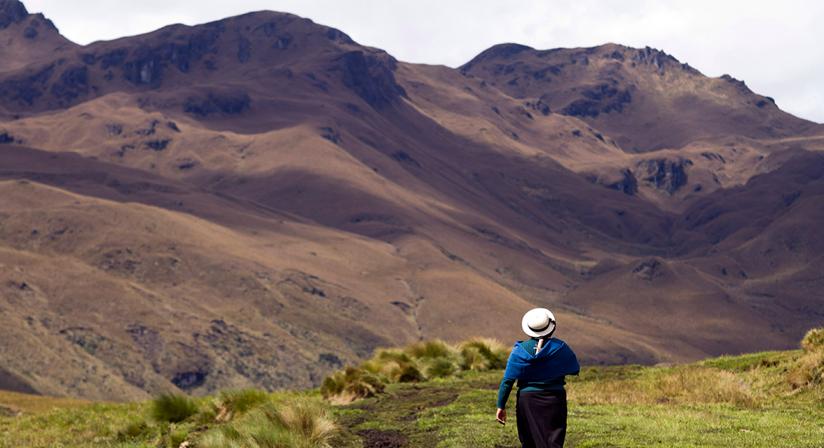 Local woman walking across the grassy fields and mountainous backdrop of Ecuador