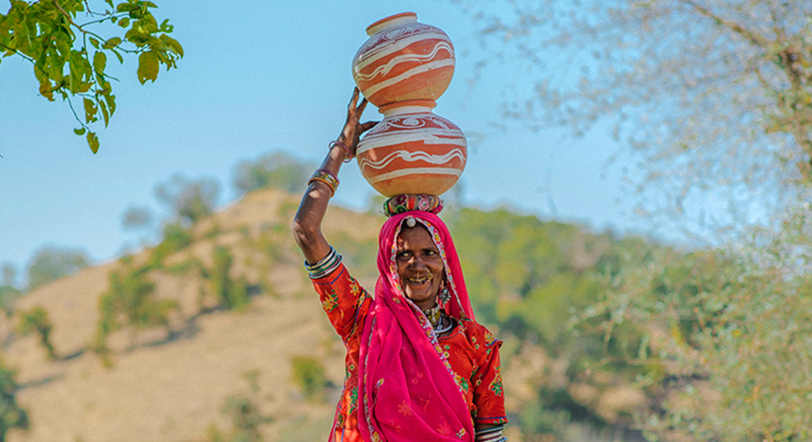 Local Indian woman balancing jugs of water in clay pots on her head in India