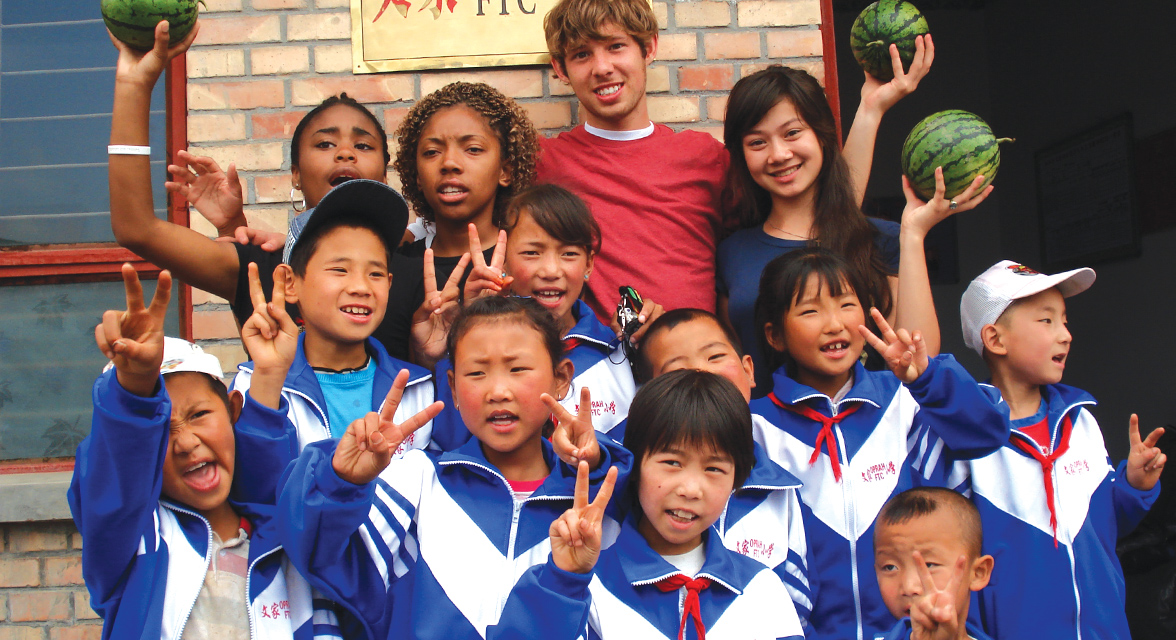 Travellers taking a picture with school children in China
