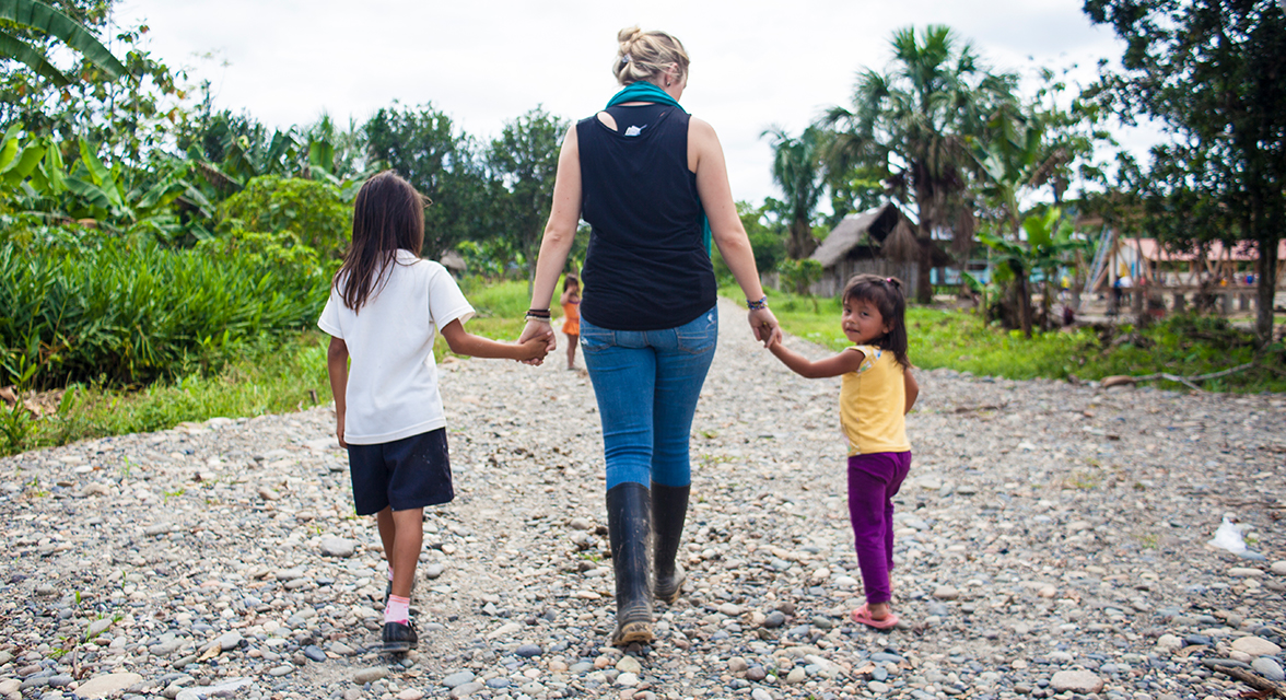 A volunteer walks with two young children in Ecuador