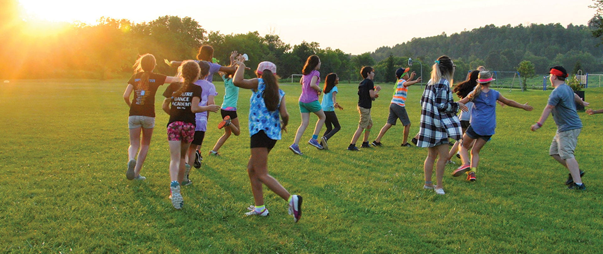 Youth playing in a field at Take Action Camp