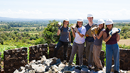 Group of young volunteering travellers holding up bricks while posing for a picture on a build site