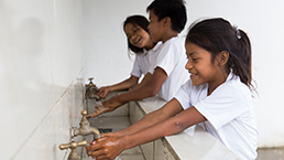 Young local students washing their hands