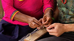 Local woman teaching traveller traditional beading on a small loom