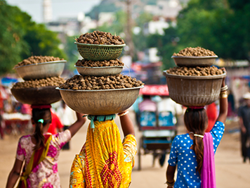 Local Indian women balancing bowls of food on their heads walking down the street