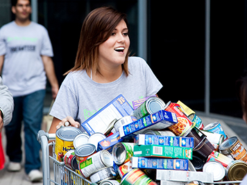 A volunteer with a cart of food donations
