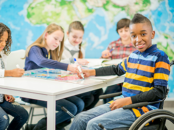 A student sitting in a wheel chair in his classroom
