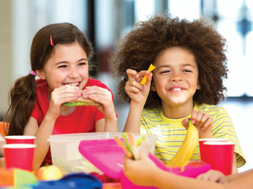 Young students eating healthy snacks