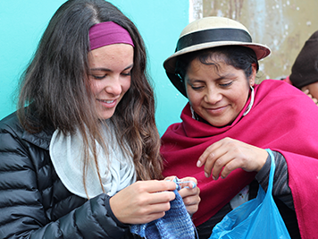 Local Ecuadorian woman teaching young traveller how to knit