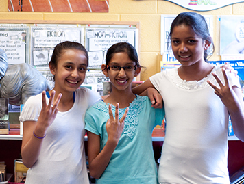 WE Schools students holding the WE sign at school