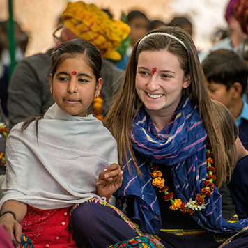 Young traveller sitting with a local girl