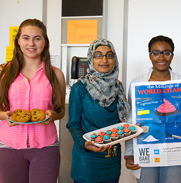 Students promoting WE Bake for Change with baked goods and poster