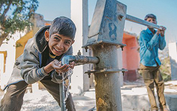 A young boy pumps water into the hands of another.
