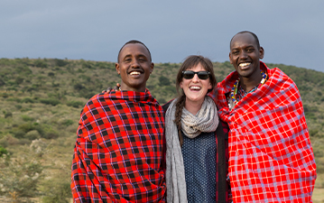 Maasai Warrior teaching traveller to shoot traditional bow and arrow in Kenya