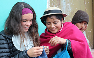 Local Ecuadorian woman showing young traveller how to knit