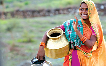 Local woman carrying water jugs in India