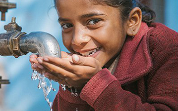 A young girl drinks from a clean water tap.