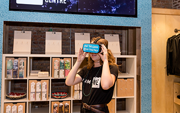 WE employee playing with a VR headset at the WE Global Learning Center gift shop
