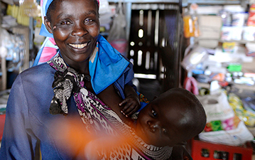 A woman smiles and holds a child in front of a fully-stocked shop.