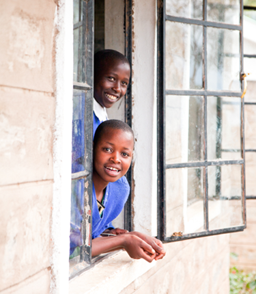 Local students looking out a window in a WE Villages partner community